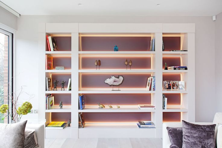 Living room display shelving with lighting at the back of the shelves. by Anmdrew Manning Furniture
