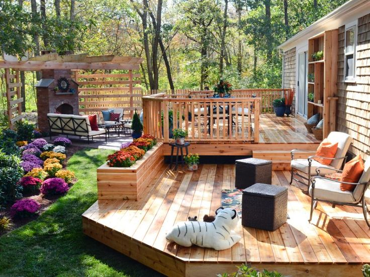 A sprawling 2-level cedar deck and brick patio anchored by an outdoor fireplace and pergola provide ample space for alfresco dining and relaxing with friends or family. To soften all the hardscape, Chris Lambton and crew pushed back the wooded area to make room for a sinuous bed filled with perennials for year-round appeal and blooming annuals for color.