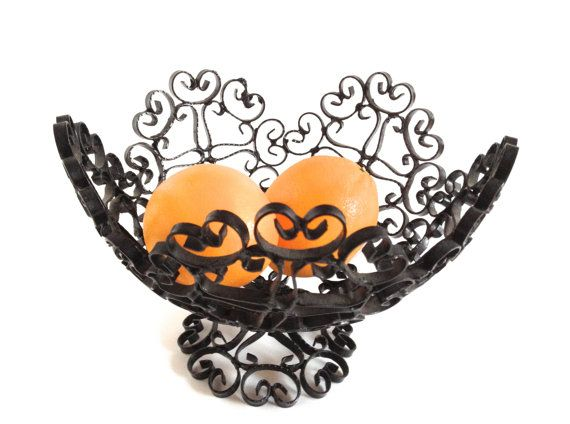 Pretty iron basket holds fruit, rolls, or decorative items. Made in Spain, it stands 6 high and 9 across. Curly black coated metal adds a Spanish