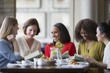 Women friends discussing book club book at restaurant table - Caiaimage/Martin Baurraud / Getty Images