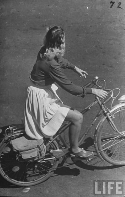 French girl riding a bicycle.  Location: France  Date taken: 1945  Photographer: Ralph Morse