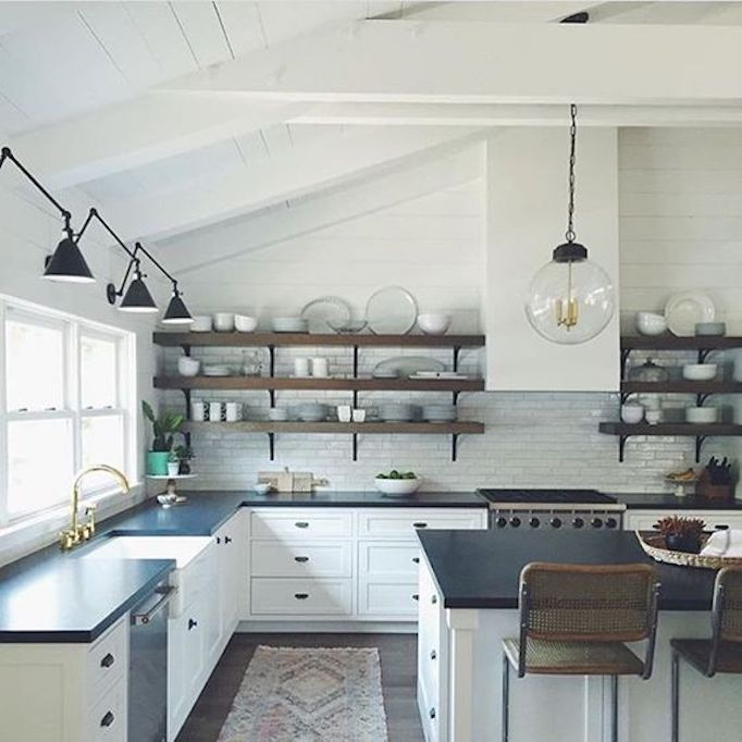 BECKI OWENS--Colors of the Modern Farmhouse + Paint Guide. Beautiful white Farmhouse kitchen with open shelving, dark counters, library sconces and globe pendants.