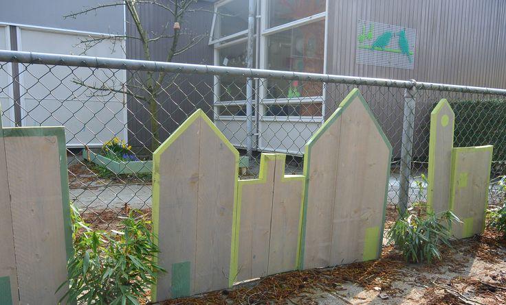 Het lelijke hek wordt weggewerkt met houten huisjes en bamboe