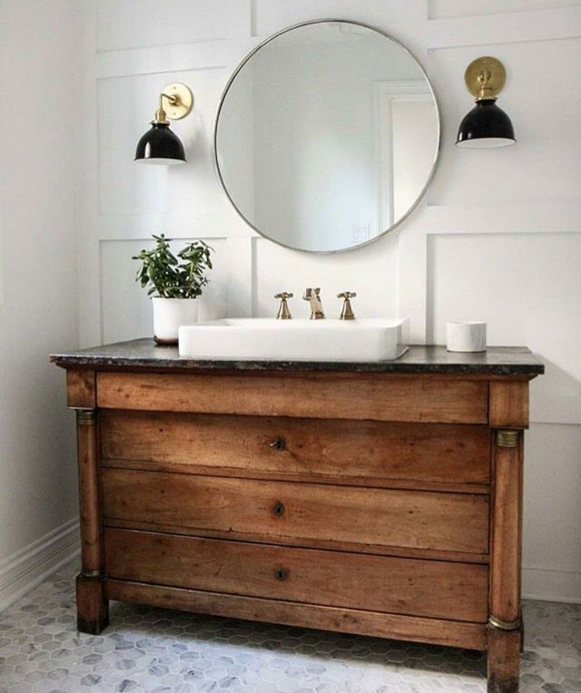 white bathroom with pattern tile, board and batten wall, round mirror and black with brass sconce.