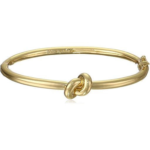 Kate Spade New York Gold-Tone Brass Knot Bangle Bracelet This delicate and simple sailors knot bangle bracelet by Kate Spade New York is inspired by romantic design. This wholesale fashion jewelry is made entirely of brass with gold-tone finish. Measuring 0.13 inches wide the bangle features safety clasp for securing. Because this is a bracelet this Kate Spade New York brass knot bangle bracelet represents the pinnacle of style and grace. This remarkable bangle is simple yet classy so you…