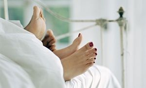 Couple lying in bed, feet sticking out of covers