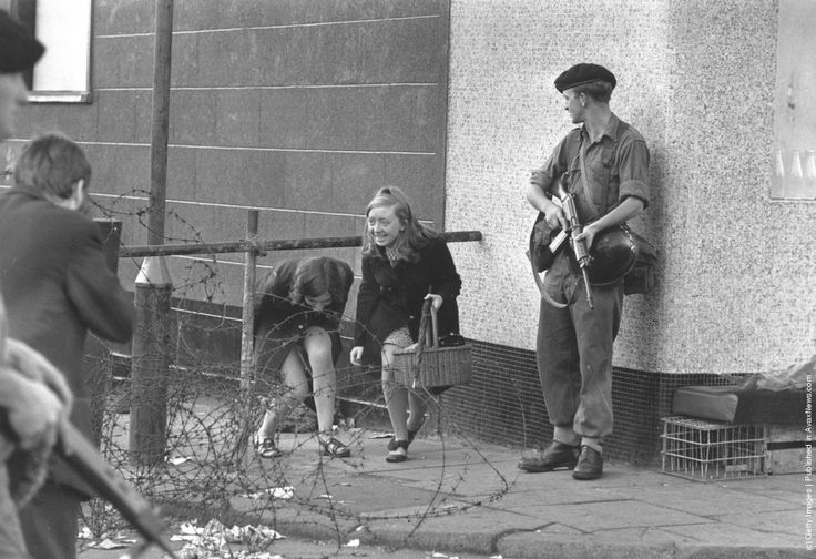 young women climbing under a barricade next to an armed soldier on the Falls Road, Belfast. (Photo by Evening Standard/Getty Images). 16th August 1969