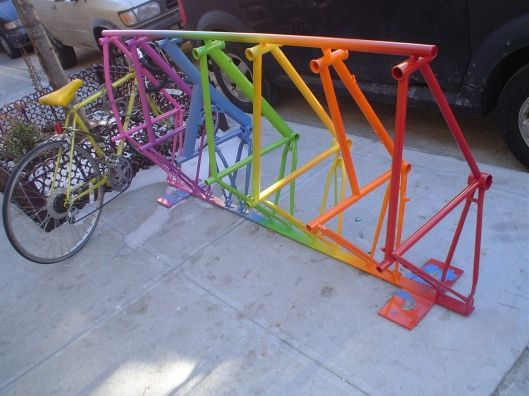A #bike rack made out of colorful bike frames.
