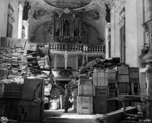 Tweede Wereldoorlog, kunstroof nazi-Duitsland. Een Amerikaanse soldaat van de US Third Army, 86e divisie, staat tussen door Duitsers gestolen kunst in een kerk in Ellingen, Duitsland. 24 april 1945.