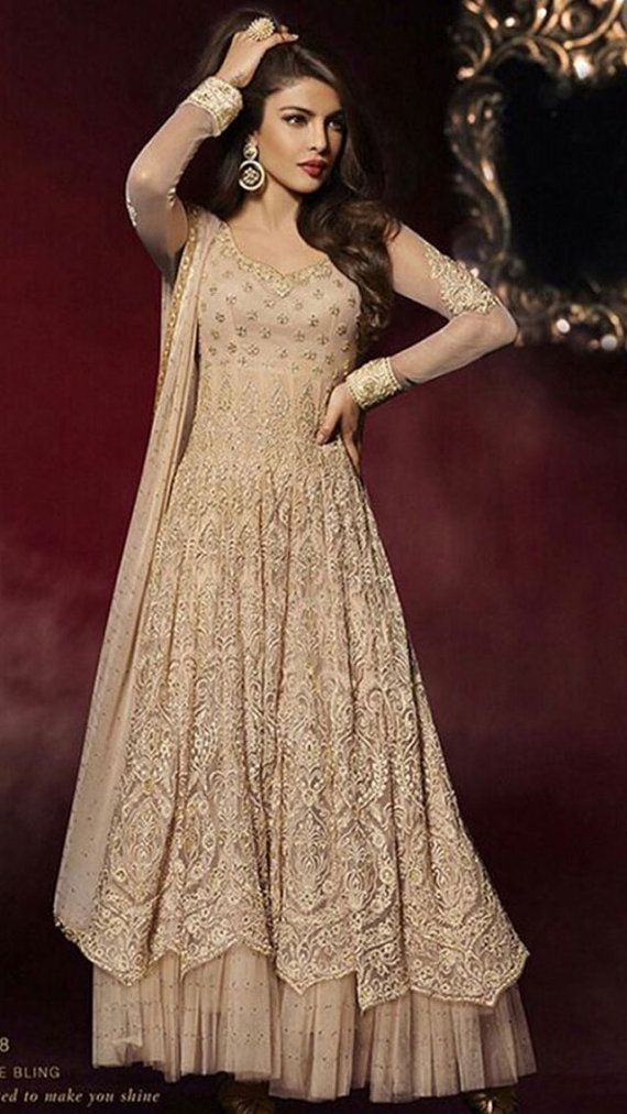 Original. Out of production.  Stitched and ready to wear anarkali suits in beige net. Handwork in thread, stones, zari on fabric and laces. One piece