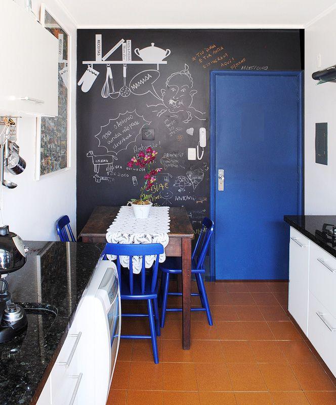 """""""Na reforma desta cozinha removemos os antigos azulejos da parede e mantivemos o piso. Nas paredes: lousa em esmalte acetinado preto, painel de cerâmicas coloridas sobre cooktop e todo o restante em branco. Esquadrias em azul intenso para contraste."""", diz Thais Lenzi."""