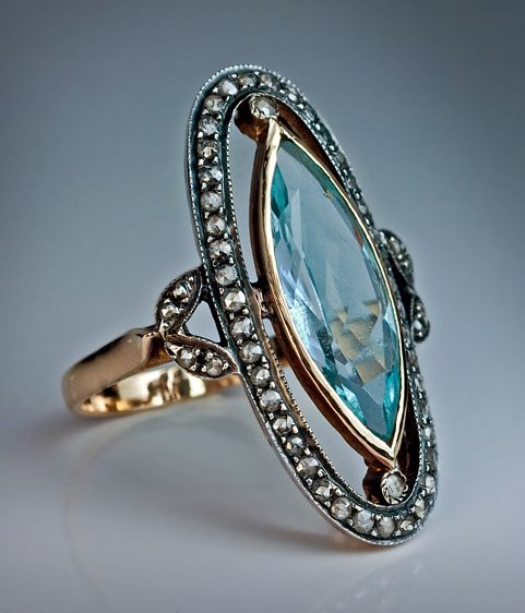 An Edwardian Era Antique Aquamarine and Diamond Long Ring  circa 1910  The ring features a navette (marquise) cut aquamarine (approximately 3.92 carats - 19 x 8.5 x 4.4 mm),   set in a yellow gold bezel within an oval rose cut diamond frame.   The shoulders are embellished with stylized leaves with rose cut diamonds.  The 52 rose diamonds are set in silver over gold.