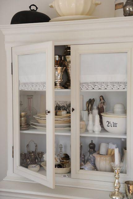 Fabric in glass doors to hide shelves.