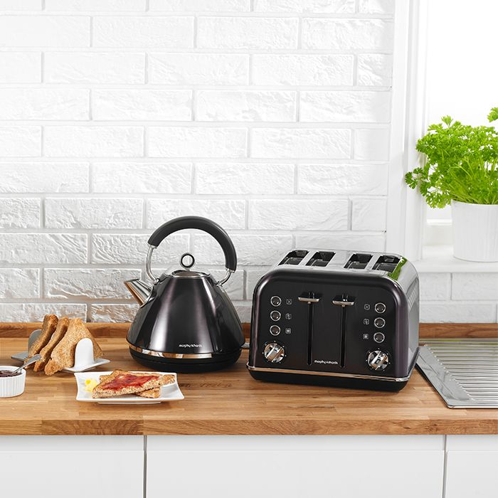 The Accents Traditional Pyramid Kettle & 4 Slice toaster set is a stylish statement for any kitchen, featuring painted stainless steel bodies in black and chrome accents for a modern metallic touch. Add a worthy accent to your interior design with Morphy Richards.
