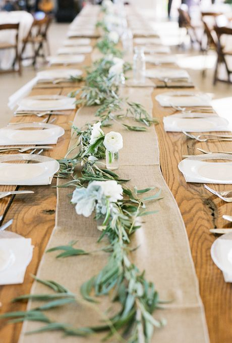 Rustic table runner with olive branch stems and fluffy white flowers
