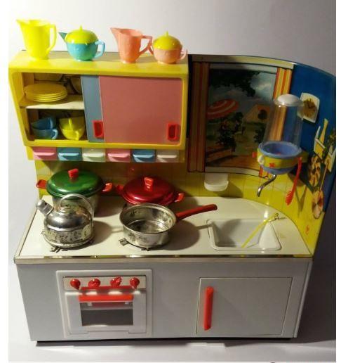 Het blikken keukentje van het Duitse merk Fuchs dat ik vroeger had, lijkt heel erg op deze uitvoering.  Koken op witte blokjes die konden branden, een namaak-kip in de oven, waterkraan, plastic mini servies (volgens mij had ik alleen de pastelkleuren roze en blauw)
