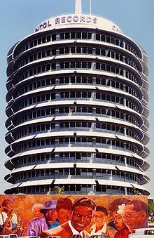 """During his tenure at Capitol Records, Nat """"King"""" Cole's sales fueled much of the Record Company's success.  In fact, it was his record sales revenues that are believed to have played a significant role in financing the distinctive Capitol Records building, near Hollywood and Vine, in Los Angeles. Completed in 1956, it was the world's first circular office building and it became known as """"The House that Nat Built""""."""