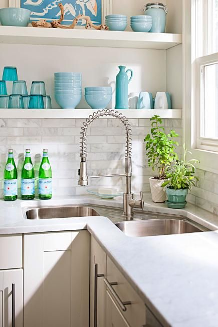 corner kitchen sink. save space of corners being unused green glass on shelves pearl tiles