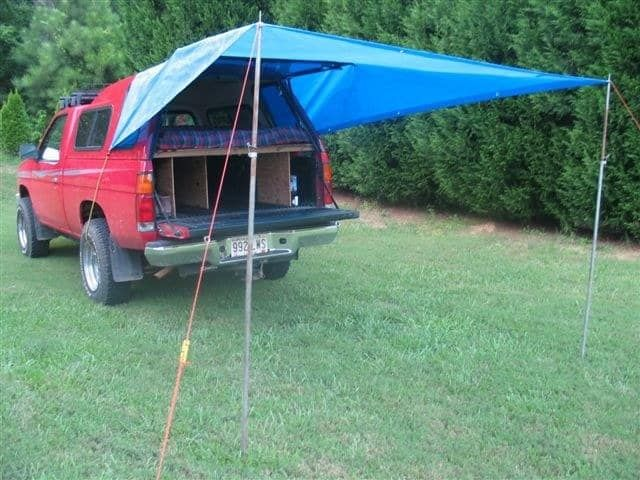 8. Then boost up the tarp with two poles or sticks to make a covered porch for sitting, eating, and shade.