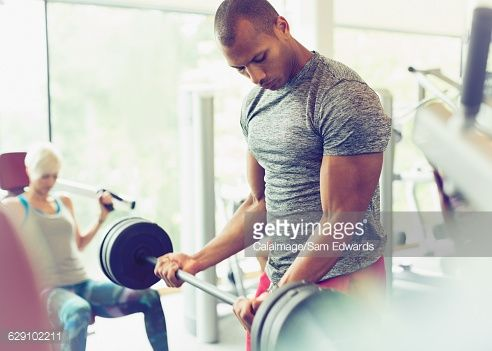 Focused man doing barbell biceps curls at gym