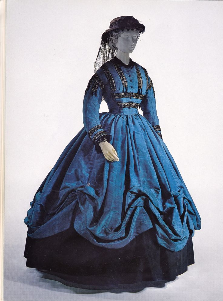 The text that accompanies this photo is as follows: American walking dress, c. 1864, of blue watered silk, trimmed with black lace, white ribbon, and jet beads. metal rings sewn into the seams are...
