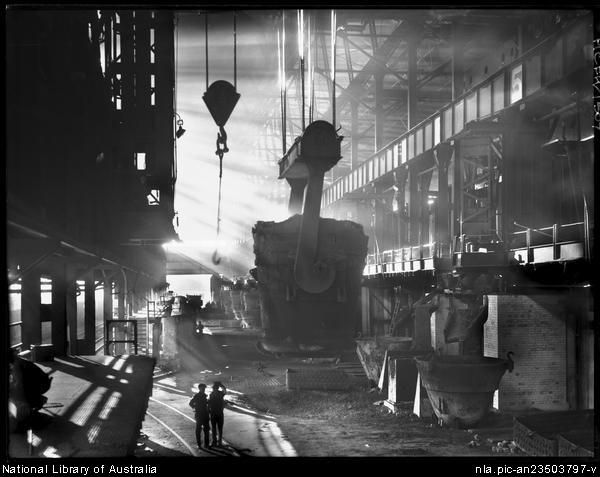An eighty-ton ladle in the open hearth pit being carried to the furnace  at B.H.P. Steelworks, Newcastle - Frank Hurley (NLA)