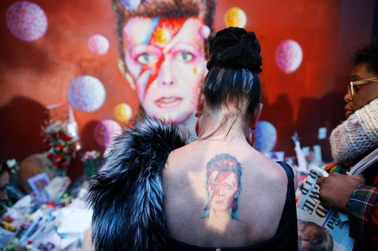 A woman with a Ziggy Stardust tattoo visits a mural of David Bowie in Brixton, south London, the day after his death, on January 11.