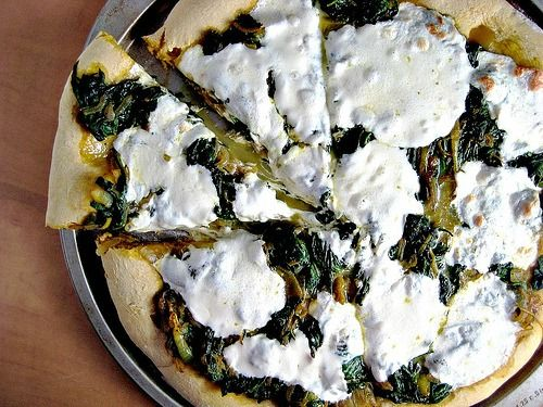 spinach and onion curry pizza on a pumpkin pizza dough crust