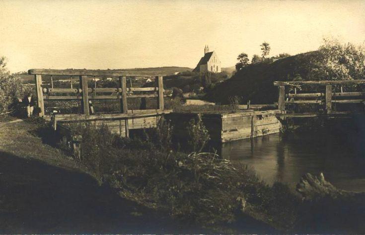 Pod de lemn cu stavilar, peste Canalul Morii la inceputul sec.XX. In plan indepartat Biserica Romano Catolica Calvaria.  Sursa: szabadsag.ro