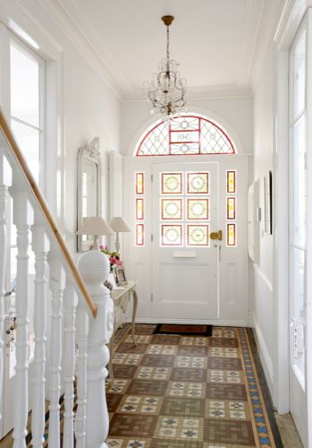 A narrow entrance hall in this London Victorian home is brightened with all-over white paint, and made interesting with colorful accents in the patterned floors and stained glass windows  (via White Location | Home)