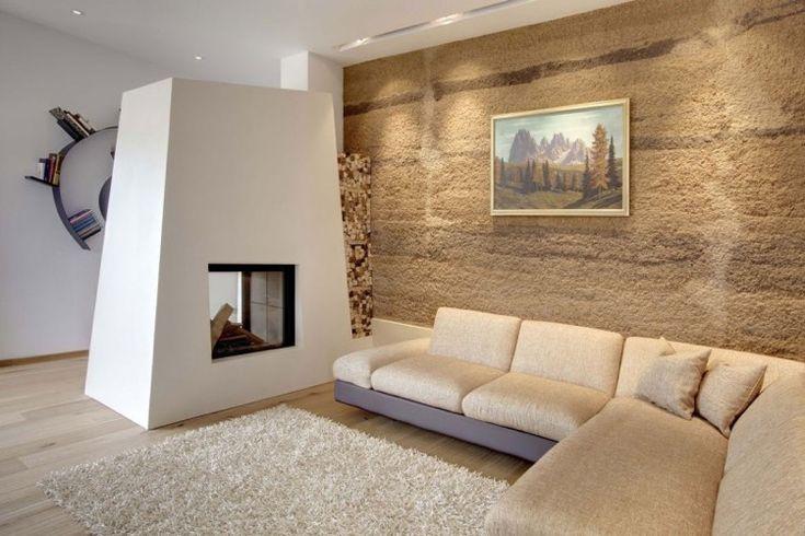 salon minimaliste élégant aménagé avec un mur de pierre naturelle, une cheminée deux faces et un canapé d'angle beige