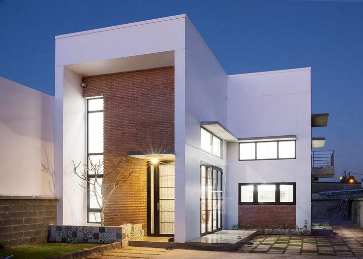 Thick brick wall gives the facade of the house a unique modern industrial look