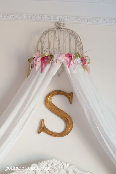 This bed canopy was built from a planter, ribbon and IKEA drapes. I just hung the planter upside down on the wall. I then sewed ribbon to the top of the IKEA drapes to attach the drapes to the planter.