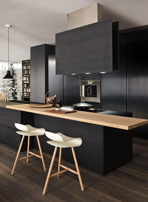Chic black kitchen countertops with black oven hood and the contrast of white low profile barstools.