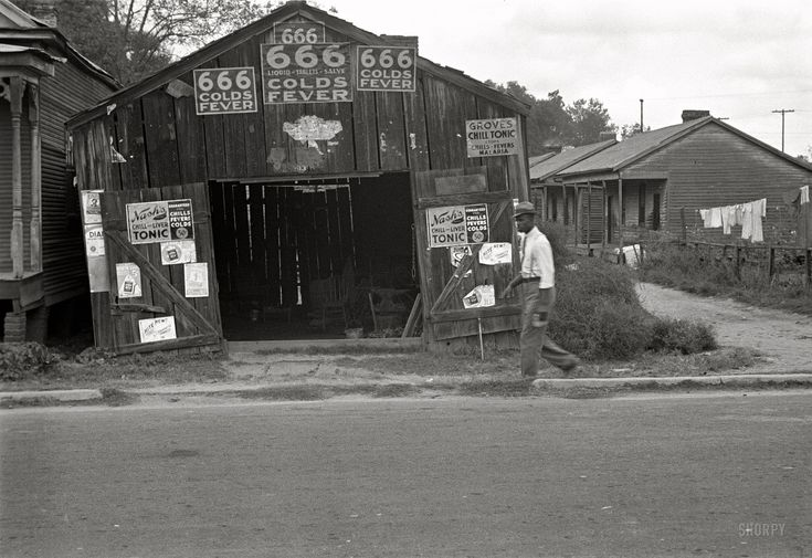 "October 1935. ""Advertisements for popular malaria cure. Natchez, Mississippi."" Photo by Ben Shahn for the Farm Security Administration."