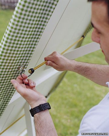 Insert grommets onto a tablecloth, then use bungee cords to keep it from lifting up in the wind.  omg! genius!