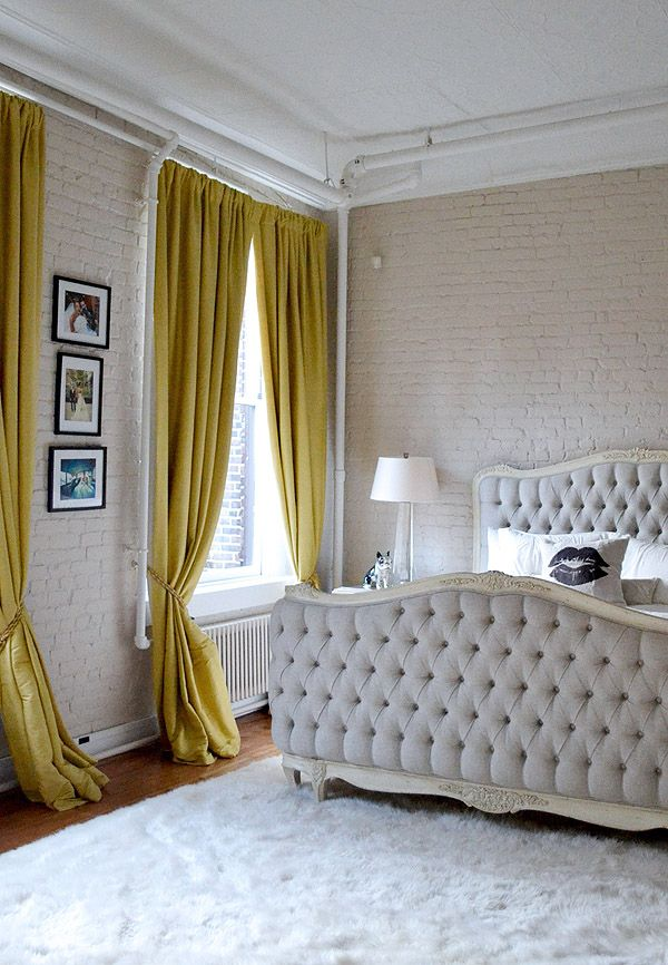 Soho NYC loft Tamra Sanford bedroom brick walls mustard drapes tufted bed