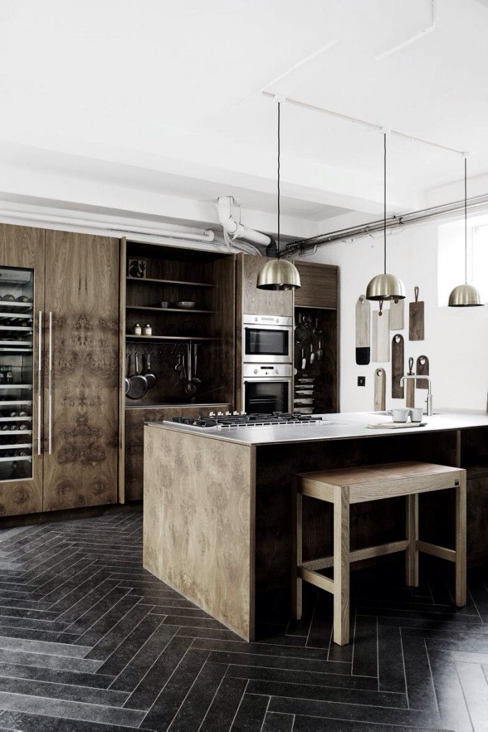 The timber cabinets and black herringbone floor tiles give this kitchen a real moody look. The pendant lights and the different chopping boards hanging against the wall finish this kitchen off nicely.