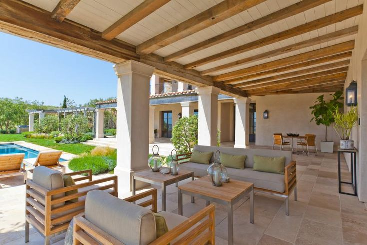 Designers were able to successfully mix styles by keeping with the home's exterior neutral color scheme across the outdoor furniture and accessories. The more contemporary patio furniture blends well with the French Provincial theme because it does not take a lead in the overall scheme; rather, the furniture's simple lines and structure blend with the evenness of the architecture. Landscaping by Mark Scott and Associates.