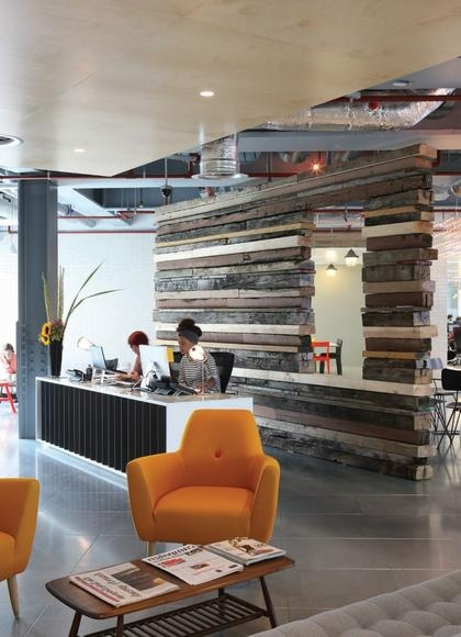 The reception of Glue Isobar, with a feature wall created out of reclaimed railway sleepers, and a customised desk - Aegis office