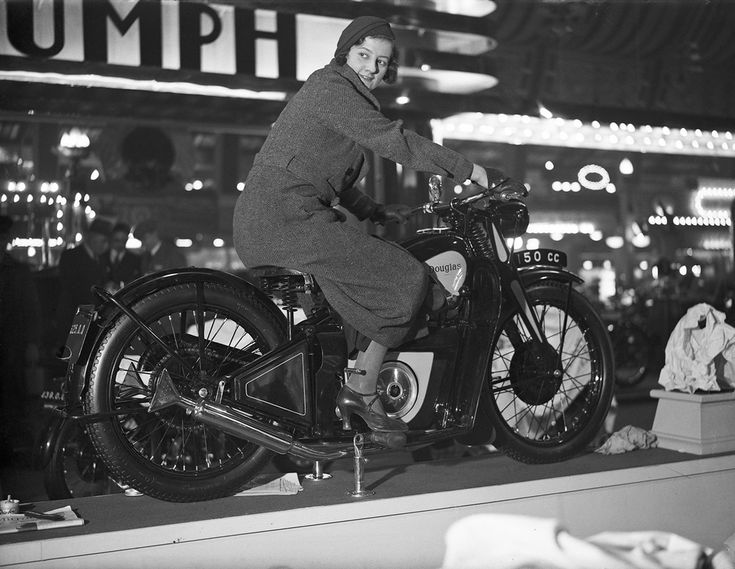 A woman trying out a Douglas motorcycle on display at the 18th Cycle and Motorcycle Show in London, 1933.