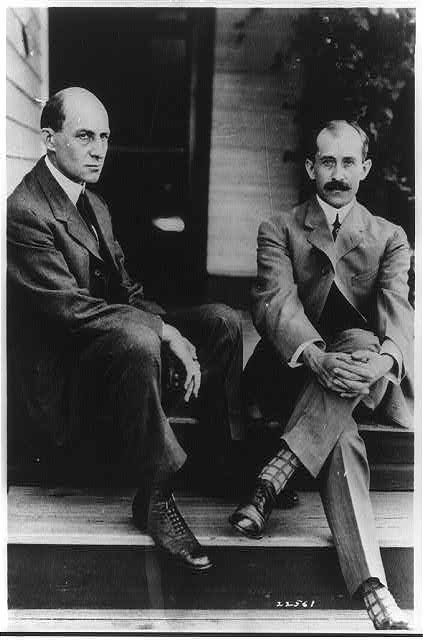 Wilbur Wright and Orville Wright seated on steps of rear ...