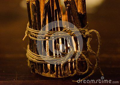Close-up of creative candle holder decorated with twigs and craft rope keeping light of burning candle.