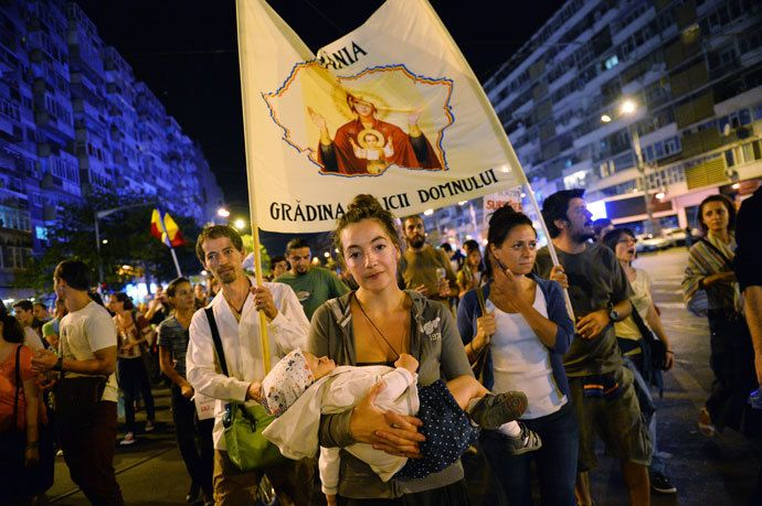 Protesters march and hold banners during the eighth day of demonstrations in Bucharest against the Rosia Montana Gold Corporation (RMGC), a Canadian gold mine project using cyanide, on September 8, 2013.(AFP Photo / Daniel Mihascu)
