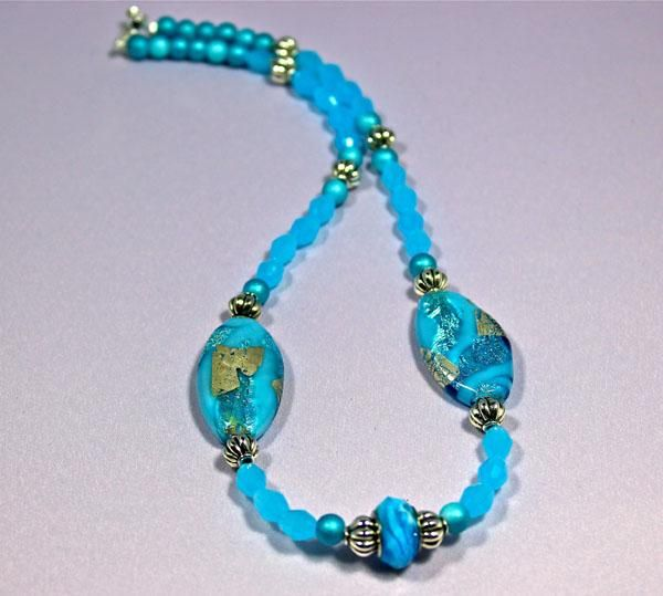 Hand made sky blue necklace with silver filled glass and Murano Glass bead in the center strung with blue crystals.
