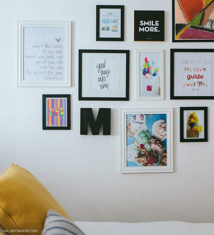 Parede com composição de quadros com frases, ilustrações e fotografias alegram o quarto de casal.