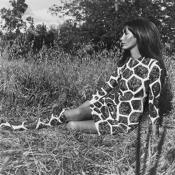 Mme Philippe Leroy reclining on the grass wearing sequined giraffeprint dress and matching boots by Laura Aponte coiffure by Wayne of Elizabeth...