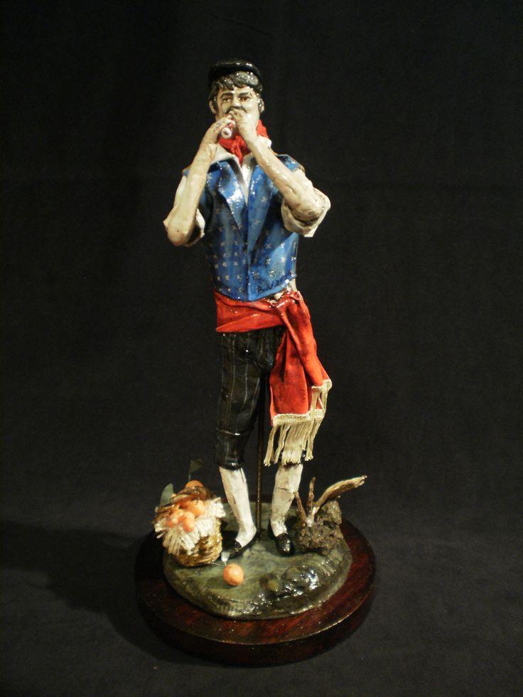 Statuetta di uomo in abiti tradizionali siciliani .L'abito veniva usato sopratutto per le festività (1830 ca.), è realizzata con cartapesta e stoffa appositamente modellata partendo da un'anima di fil di ferro.La decorazione accurata è anch'essa eseguita artigianalmente.La base è inoltre arricchita da pietra lavica e radica di fico d'india. https://www.facebook.com/WondersItaly?ref=hl