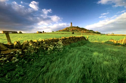 Castle Hill overlooks the large market town of Huddersfield in West Yorkshire, England. This Iron Age hill fort was constructed in 555 B.C, taking up the entire hilltop; and renovations were done in 43 AD, probably in response to a threat from the Roman Empire.