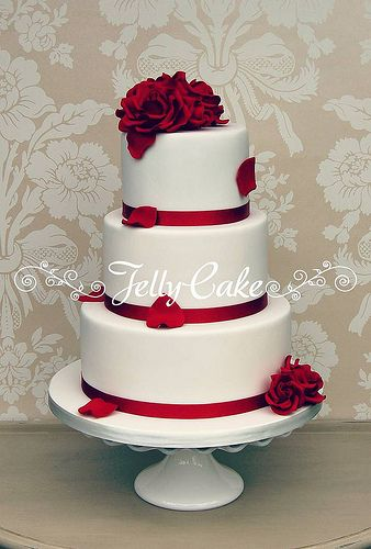 Thats exactly what i want! So you have an idea.   White with the red sash around the bottom of each layer and the red roses on it. red roses on the the top. However, I would like S and T  with a V in middle on it also.